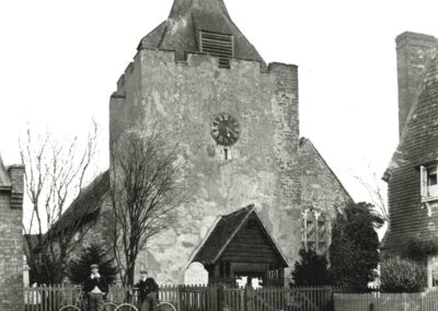Church front with two cyclists, 1900. Note the peeling plaster of the tower